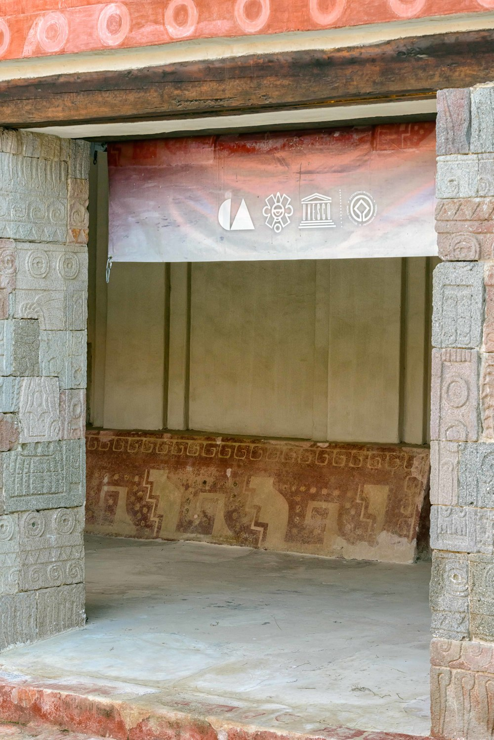 """Patio de los Pilares"", Palace of Quetzalpapalotl at Teotihuacan.  The rooms surrounding the courtyard have a porch, where you can see the review of the decoration, mainly at the bottom of the walls. The painted designs are of abstract geometric shapes, like a square stepped frets and  scrolls, and are framed by  a line of spiral-shaped ornaments, that are always in the same direction. Such designs are unique in the city."