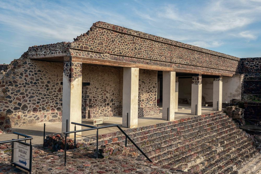 "The white columns and large jaguar head in front of the Palace of Quetzalpapalotl at Teotihuacan on the north side. Under it, buried earlier, is the ""Temple of the Feathered Conch Shells"" and adjacent, on the west side, is the ""Patio of the Jaguars."""