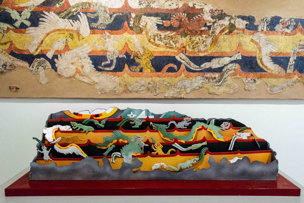 "Fragment of Mural Mythological Animals. Beatriz de la Fuente describes this mural: ""The general subject is the confrontation or simple presence (mythical or real) of animals which hide or alternate their natural image. They move, creating an undulating rhythm between the waves of water represented by wide horizontal bands of yellow, blue, or green, which alternate, separated by thin red bands which carve upwards to from peaks at regular intervals or emerging, crossing, and encircling the scaffolding of coloured bands are three classes of zoomorphic creates: quadrupeds, reptiles, and fish. Their enormously dynamic and varied positions confer dramatic movements upon the scene""."