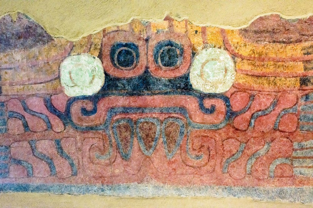 "Black Tlaloc. Th symbols by which one identities Tlaloc are the circles around the eyes, or ""googles"" and the mouth wit the corners pointing down filled with fangs, or ""moustache"". This figure with its black painted face has large circular goggles and alternating drops with elements that have been identified as flames."