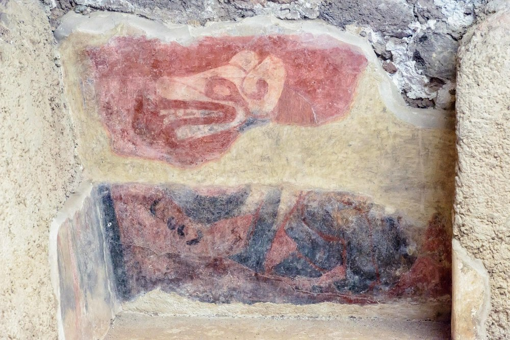 Murals with  canines. Painted on the walls of a portico and inside a room, one can observe the body of an animal in sitting position. Seen in profile, one distinguishes the canine's head with the mouth partially open, showing its teeth. a speech virgule comes out of the mouth and rolls downward.