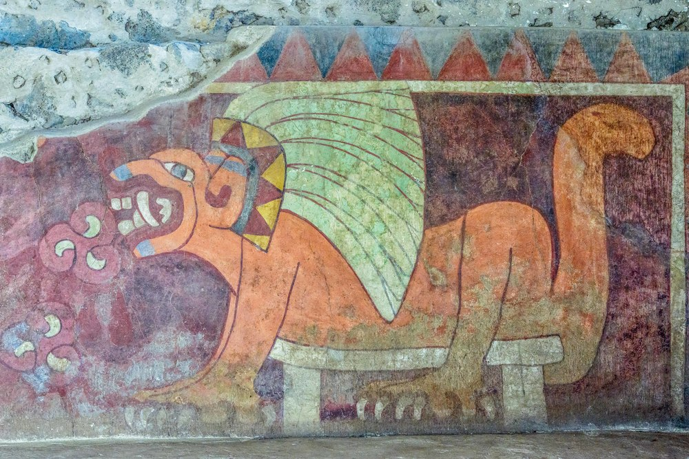 Murals with felines bearing feather headdress. Six orange felines with their stomachs resting on a bench are seen on a temple 'slope'. They bear an elaborate headdress with large feathers held by headband which is decorated with triangles and placed behind the ears. The open mouth shows large fangs and in front of these we see figures with three lobsters and red drops, which are interpreted as bleeding hearts. This allegory may indicate that the cat as deity, was given hearts to eat. The murals are delimited by a border decorated with triangles and foot prints.