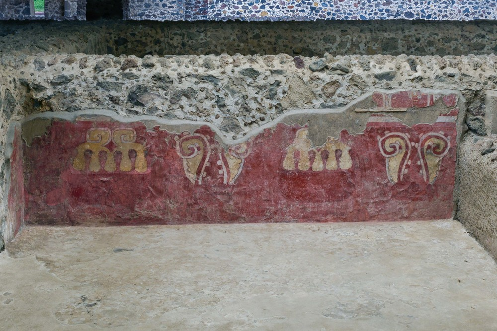 There are two designs which combine and alternate in these murals. One of them represents a mouth showing teeth from which arise two speech balloons indicating a word, chant or prayer. The other image represents two bivalve sea shells embellished with drops, symbolic elements, representing water and fertility.