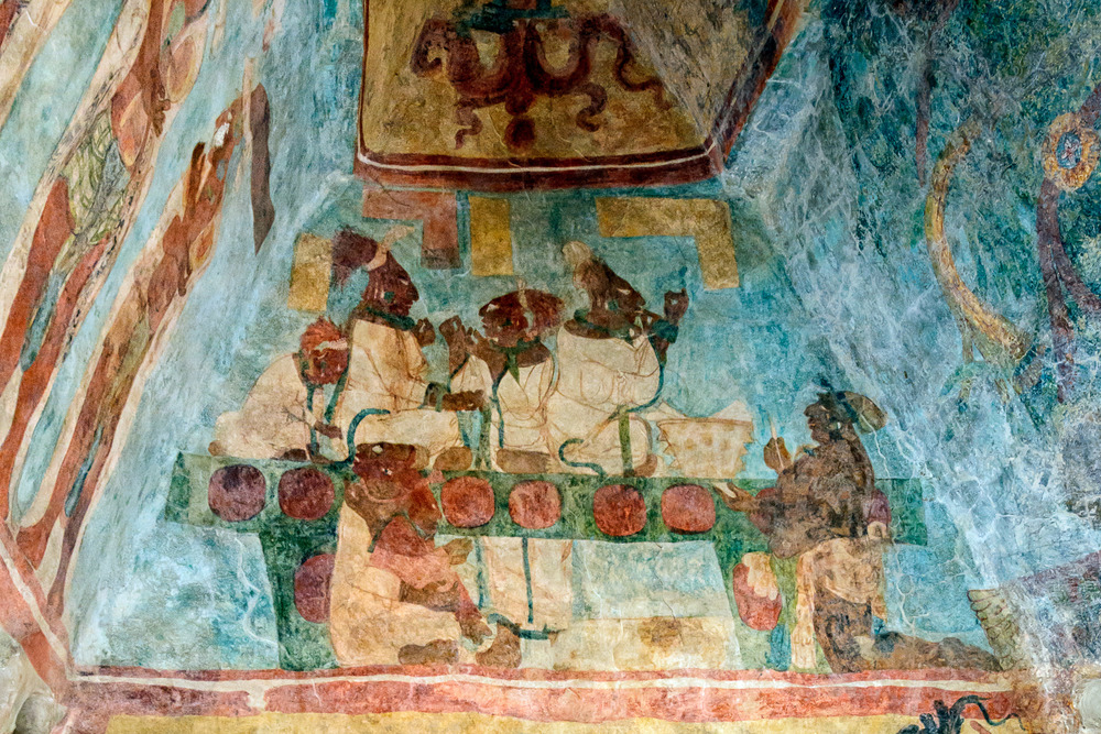 The third room of Building 1 shows a ceremony with dancers in fine costumes wearing masks of gods, and the ruler and his family stick needles into their tongues in ritual bloodletting. The accompanying hieroglyphic text dates the scene and gives the names of the principal participants.