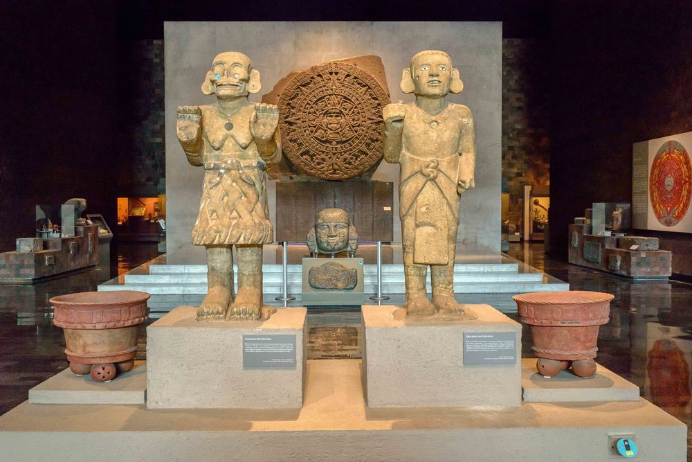 On the left the statue of the  Goddess Coatlicue  and on the right the sculpture image of this young god who could correspond to the representation of his son, Huitzilopochtli.