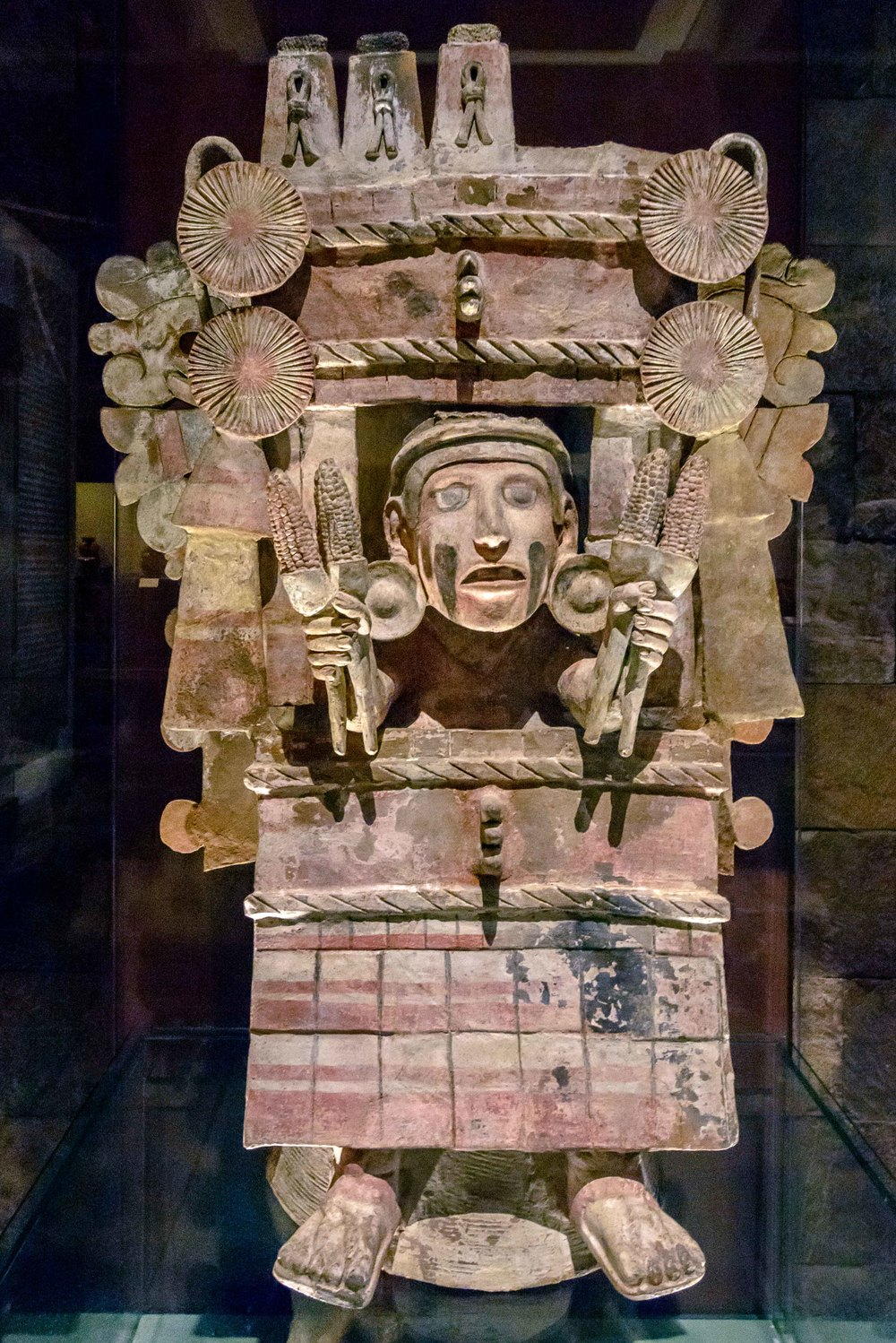 "Brasero Chicomecoatl. The red dress and headdress striking as a large cardboard box decorated with rosettes at the ends, identifies the image of this brazier Chicomecoatl, ""Seven Serpent"", the goddess of ripe corn."