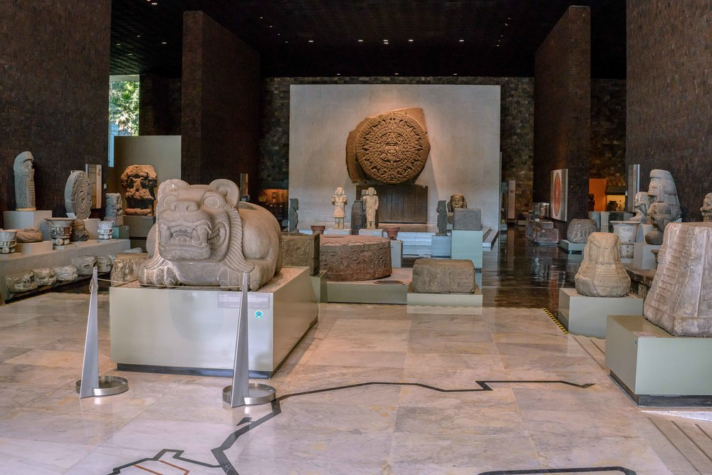 "Entrance to the ""Mexico Section"" with one of the highlight of the museum the original Aztec   ""   Stone of the Sun""  in the back.     In the front left is a  Cuauhxicalli  (meaning ""Eagle gourd bowl""), an altar-like stone vessel used by the Aztecs to contain human hearts extracted in sacrificial ceremonies. A cuahxicalli would often be decorated with animal motifs, commonly eagles or jaguars."