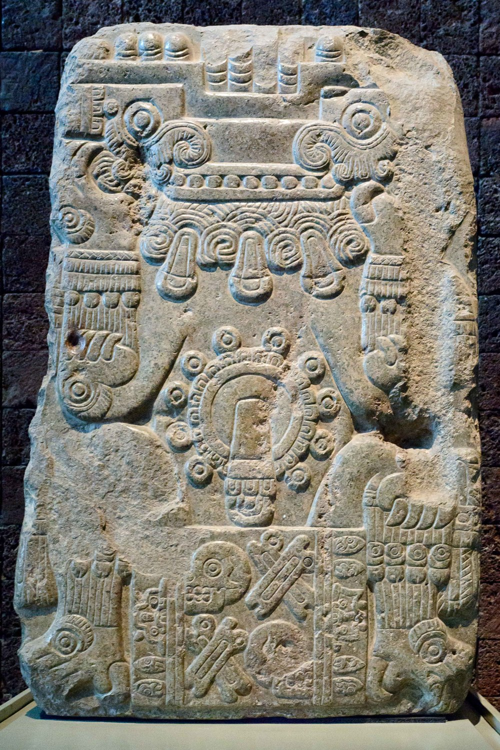 Tlaltecuhtli tombstone . Fine bas-relief representing the earth monster lurking in its characteristic position and head thrown back. The figure is adorned with anklets with bells and precious stones and wears a skirt decorated with skulls and crossbones.In the center is the jade or chalchihuite glyph, symbol of the preciousness.