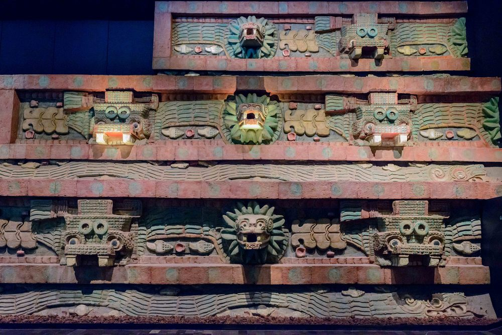"Detail of the pyramid   of the Feathered Serpent  , showing the alternating ""Tlaloc"" (left) and feathered serpent (right) heads. Note the long undulating feathered serpents in profile under the heads."