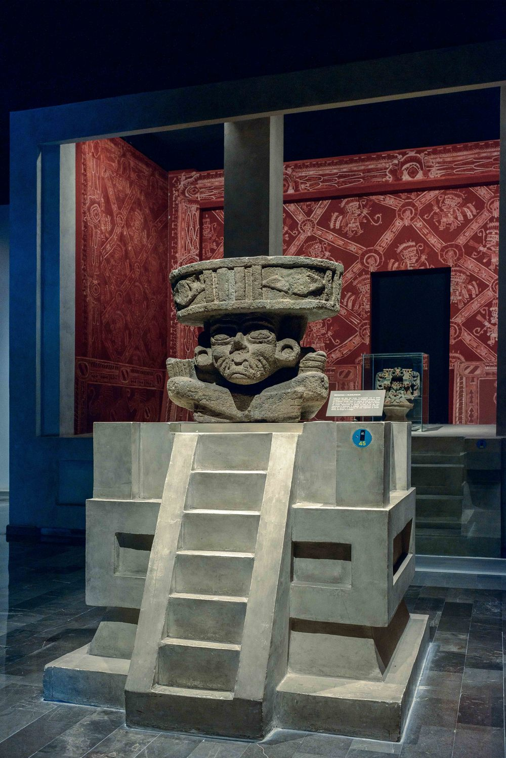 The sculpture of the fire god Huehueteotl, with wrinkled face and toothless, hunchbacked in a sitting position.