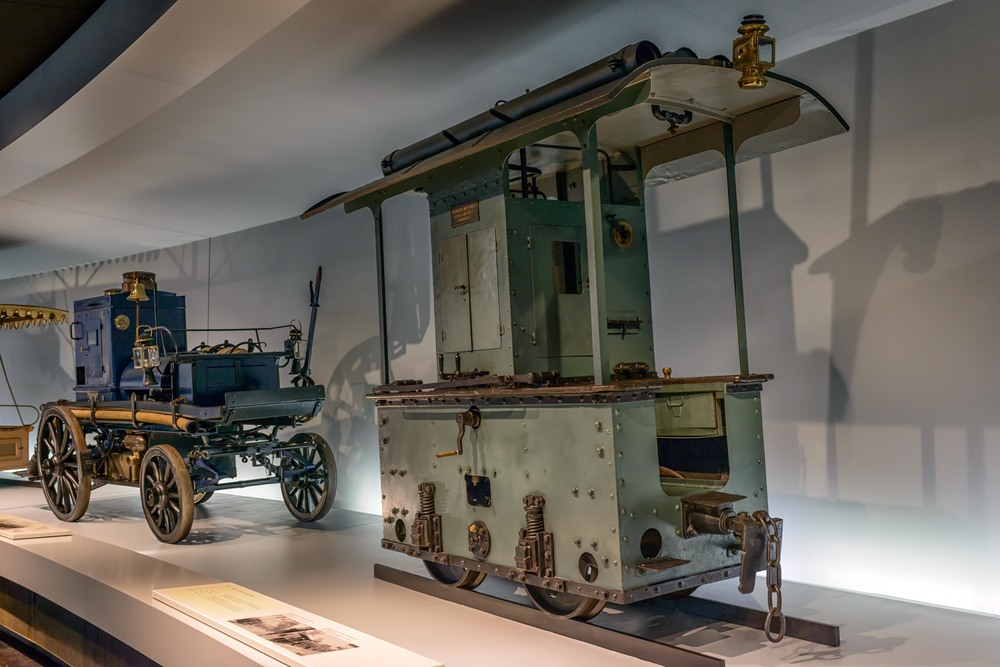Daimler motorized locomotive.   A narrow-gauge locomotive like this one, with Daimler V2 engine, was used in 1892 for an exhibition train in the Viennese Prater.  In tieback is the  Daimler motorized fire-fighting pump , one of the first of its kind with a gasoline engine.