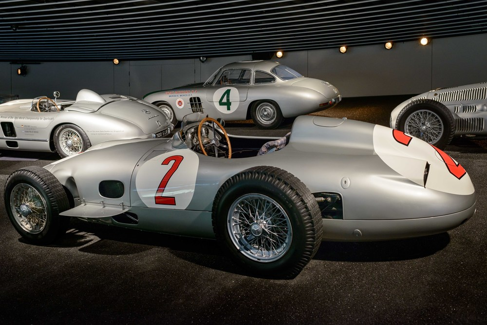 In front the  Mercedes-Benz 2,5-l-Rennwagen W 196 R.   Mercedes-Benz lined up for the Formula One races in 1954 and 1955 with two versions of the W 196 R. While the streamlined variant was selected for the high-speed circuits in Reims, Berlin and Monza, the classic monoposto with open wheels got the vote for the majority of races, as it was better suited to twistier tracks.