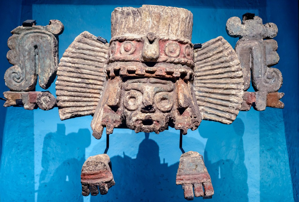 "Fragments of a Tlaloc Brazier. This polychrome brazier originally formed part of the Templo Mayor base. It shows Tlaloc's face with his typical paper headdress crowned with feathers, as well as some symbols related with fire such as the xiuhtototl (""turquoise bird""), located on his forehead."