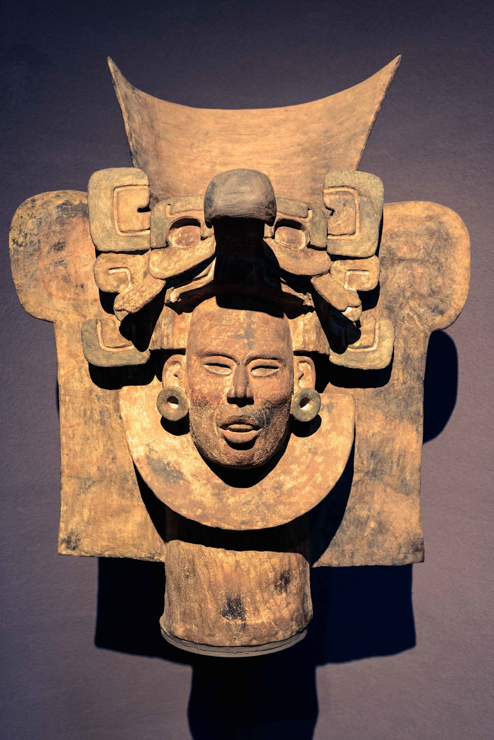 Urn. This piece shows a strong Mayan influence, apparent in the facial features depicted; an apparent cranial deformation accentuates a headdress which represents the deity known as ave del pico ancho. Tomb 77, Monte Alban, Mexico.