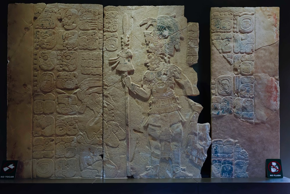 "Tablet of the Warriors. 7th Century A.D.   The scene depicts the capture of a noble called B'olon Yooj by ajaw Kan B'alam II in 695 A.D. The captive is tied in front of his subjugator, who wears a headdress with the image of the ""War Serpent"", and also holds a spear and a flexible shield. Temple XVII."