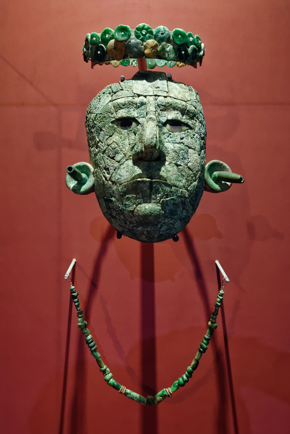 The Red Queen's Funerary Offerings. 7th Century A.D.   A mask made of malachite plaques covered this woman's face. The green colour stood for life renovation. By using funerary masks (normally made of jade), maya rulers associated themselves to the Young Maize God, who was reborn every year. The headband and necklace are jade made. Temple XIII.