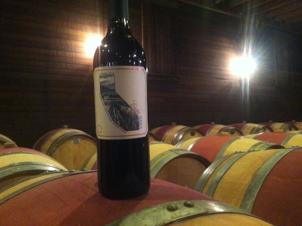 A bottle of Eight Sides Zinfandel in the cellar with its friends, the barrels.