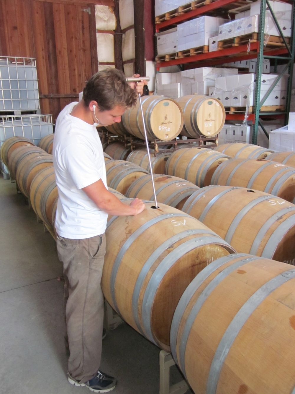 Grant stirs one of his aging wines.
