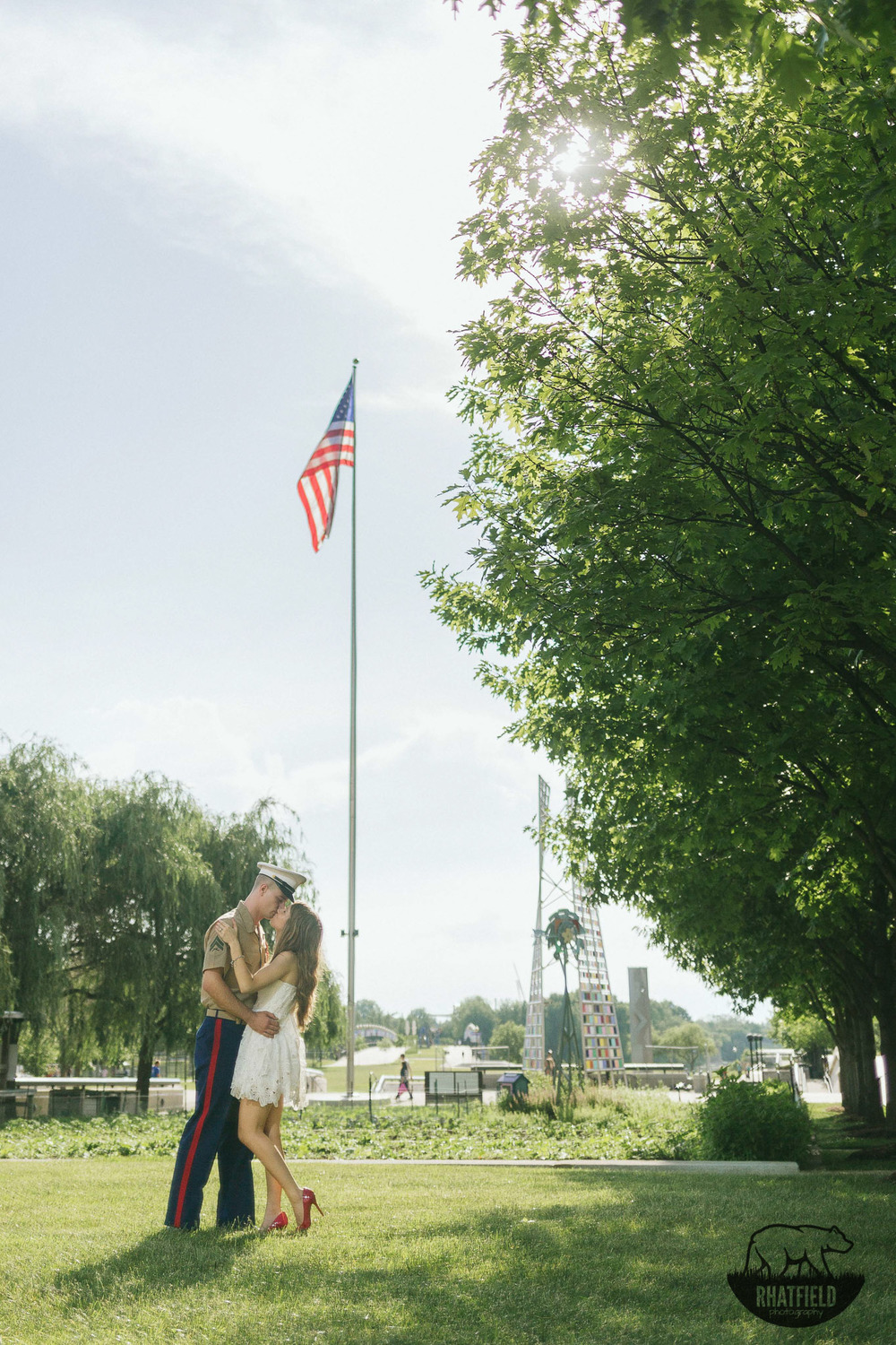 Marine-kissing-fiance-under-american-flag-park