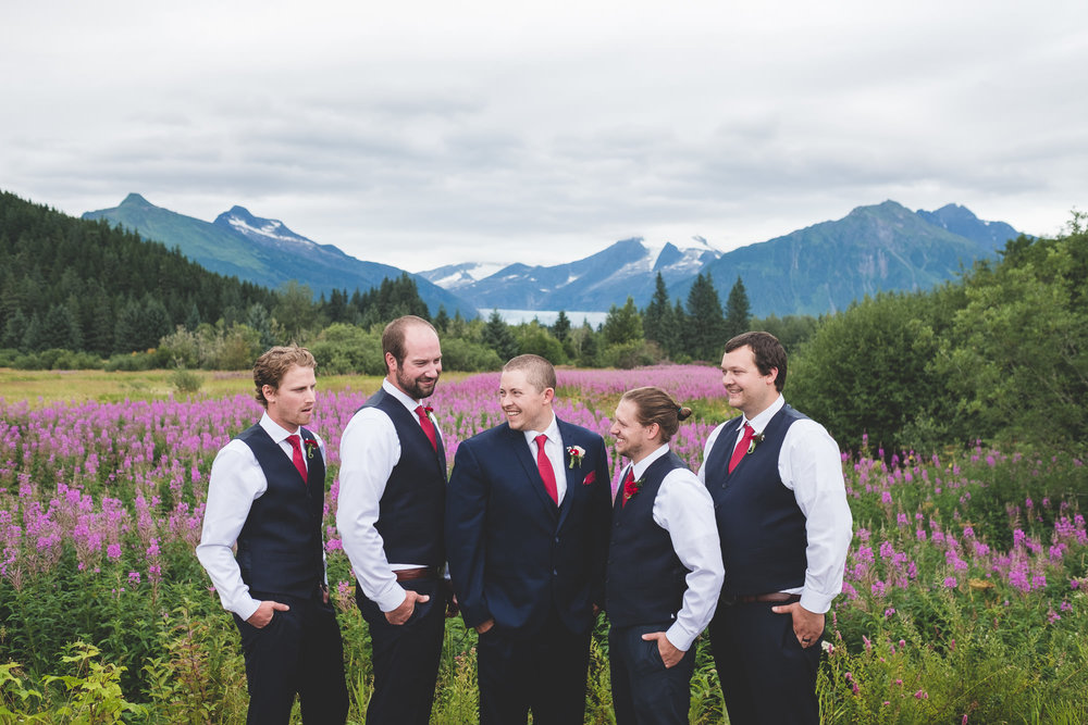 Groomsmen-laughing-together-wildflowers-and-glacier