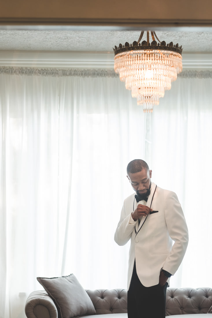 groom-wearing-white-tux-adjusting-black-pocket-square