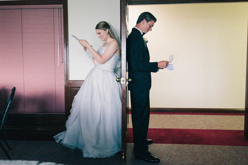 bride groom reading notes behind a door