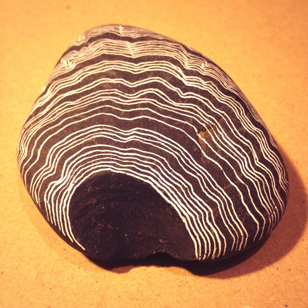 White ink on pebble