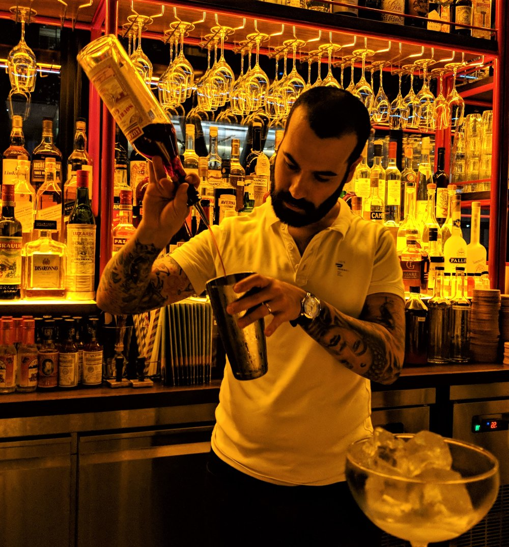 Diego pours Luxardo Sour cherry gin for a Negroni