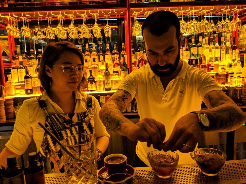 Cherrie of Caffe Fernet studies the guest bartender Diego Ferrari