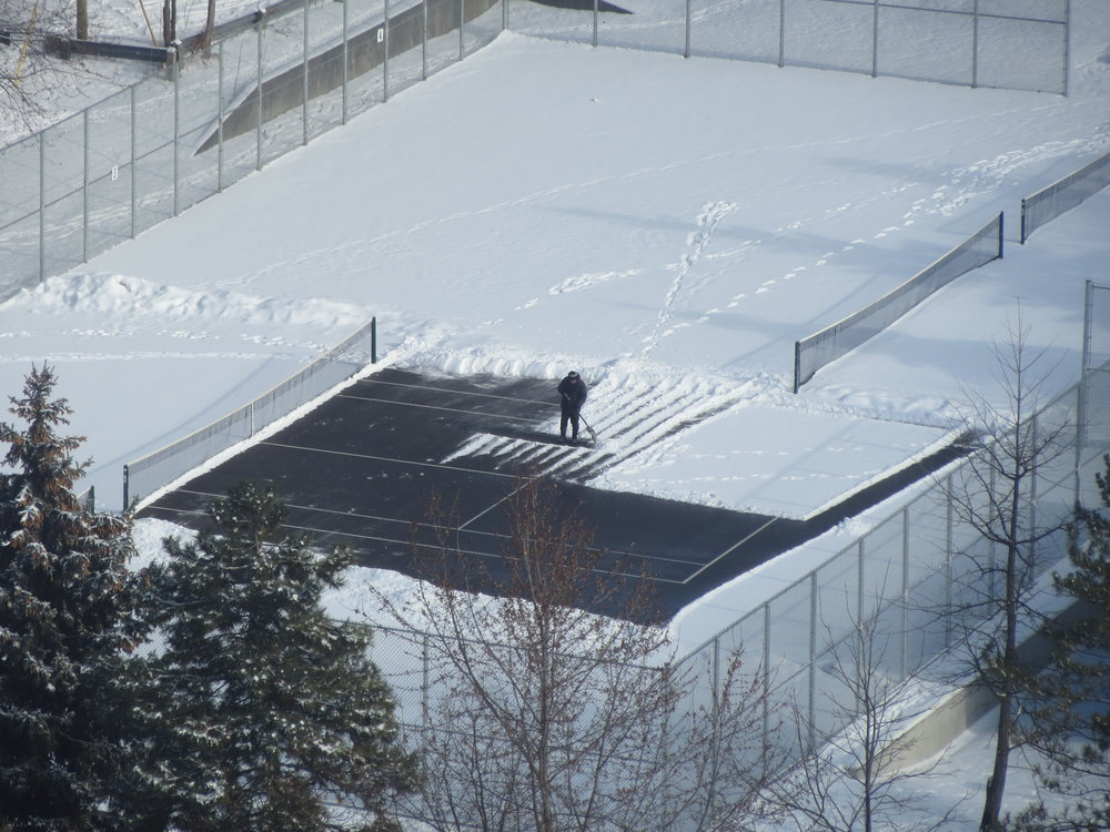 Shovelling the court.