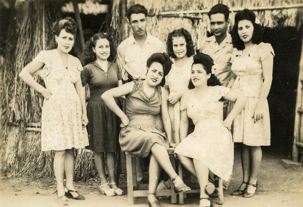 Raúl García (standing, third from left) and his wife Tomasa (standing, second from left) with friends and family in front of a tobacco house in Pueblo Nuevo, circa 1945.
