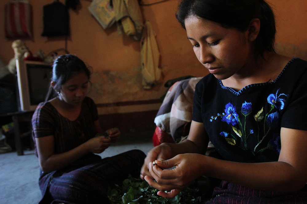 Francisca Chiviliu Quinac (right), 18, and her sister Brenda Leticia, 14, prepare dinner in their home in Santiago, Guatemala.