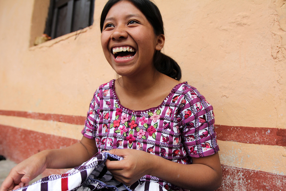 Francisca laughs as she works on embroidery outside her home.