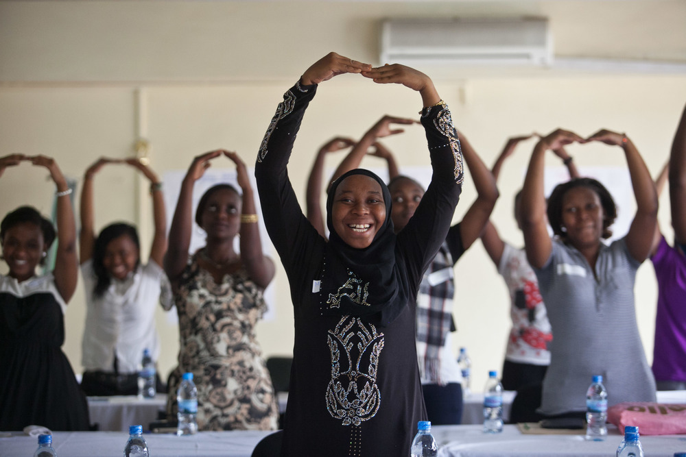Recent high school graduates participate in an icebreaker at their final mentorship meeting with AfricAid's Kisa Project