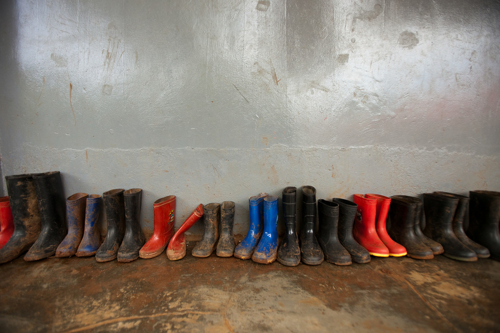 Muddy boots lined up outside a classroom.