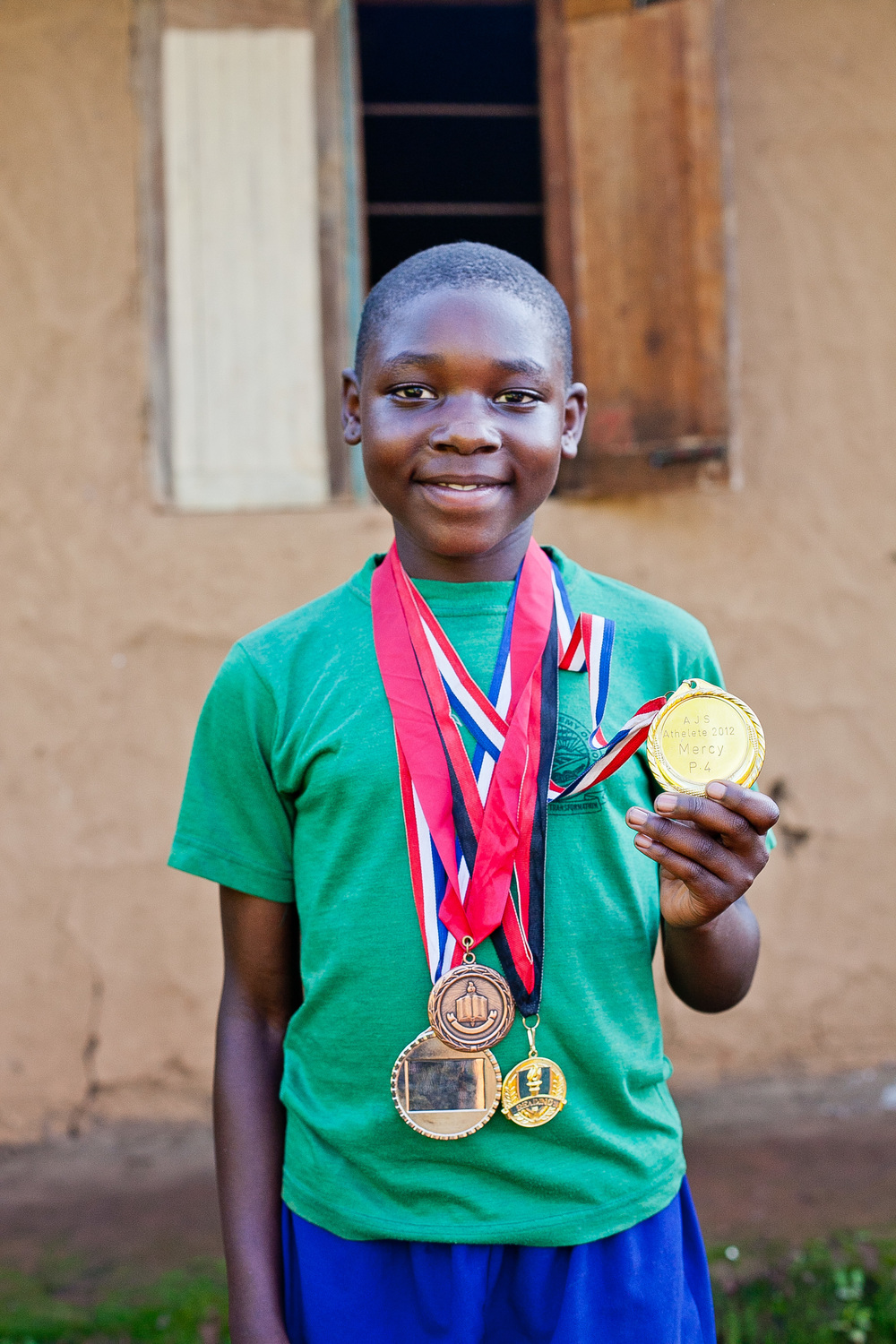 Mercy shows off some of her medals won in track competitions.