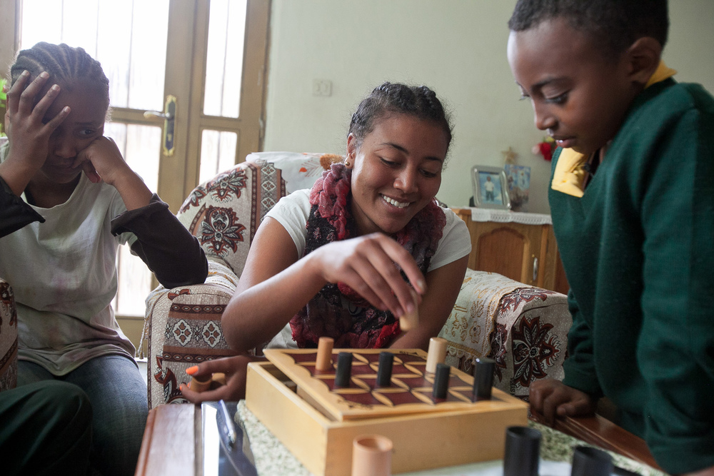 Sintayehu, center, an 18-year-old who has lived with the Selamta Family Project since she was 12, plays a game with her biological sister Senayet, left, and her Selamta brother Dagim, at their home in an Addis suburb.