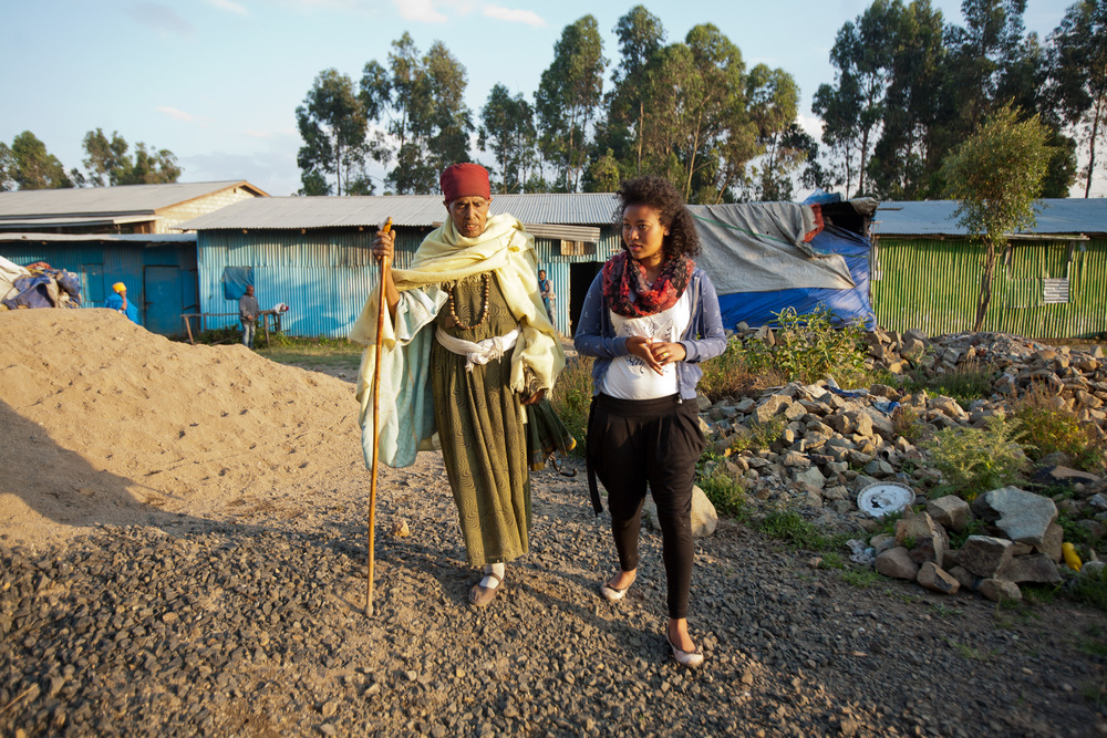 Mama Turuye, a friend of Sintayehu's grandmother, walks with Sintayehu in the impoverished area where she was living before Selamta.