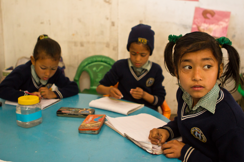 She's the First Scholar and first grader Pushpa R., right, copies from the board in class in Nepal, March 2015. (photo by Kate Lord)