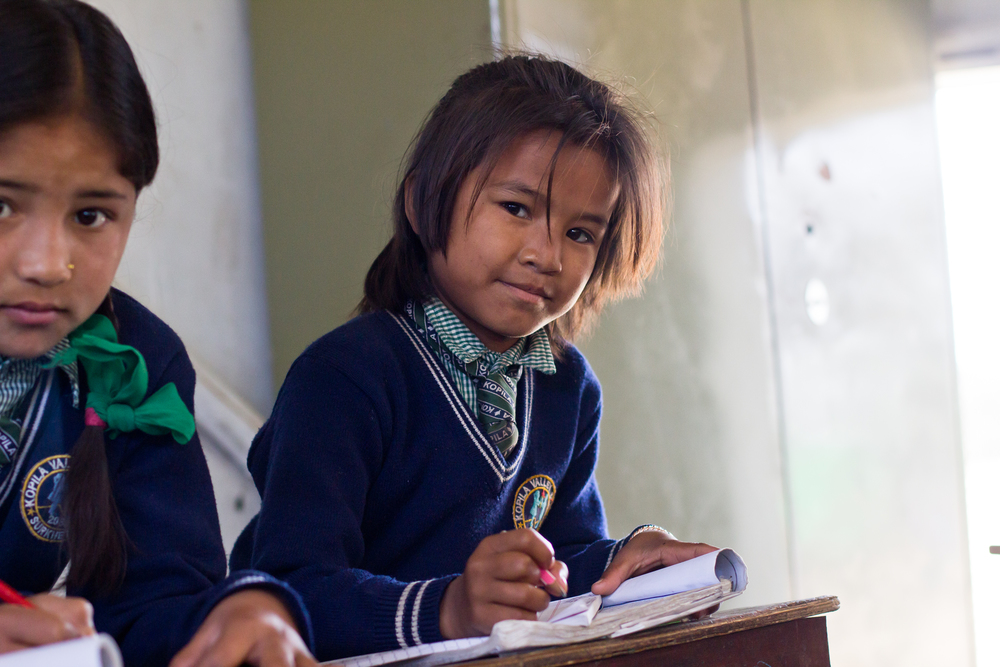 She's the First Scholar and second grader Anisha B., right, concentrates on her studies in Nepal, March 2015. (photo by Kate Lord)