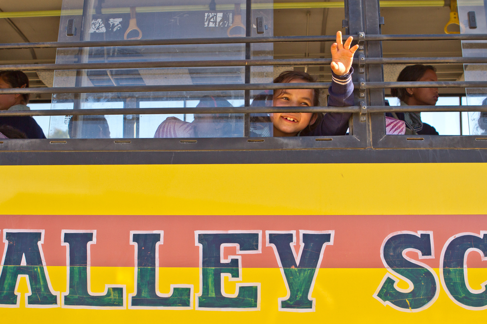She's the First Scholar Jenisha S. waves from the Kopila Valley school bus in Nepal, March 2015. (photo by Kate Lord)