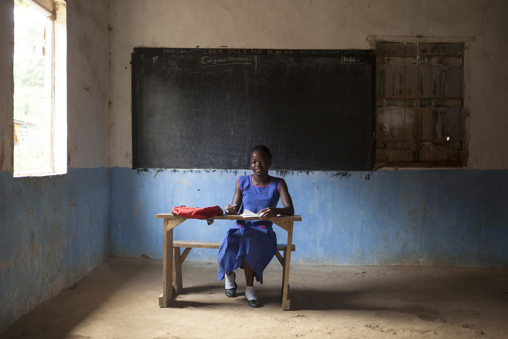 Yeanoh, 15, poses in her classroom. She loves reading, singing, and dancing.
