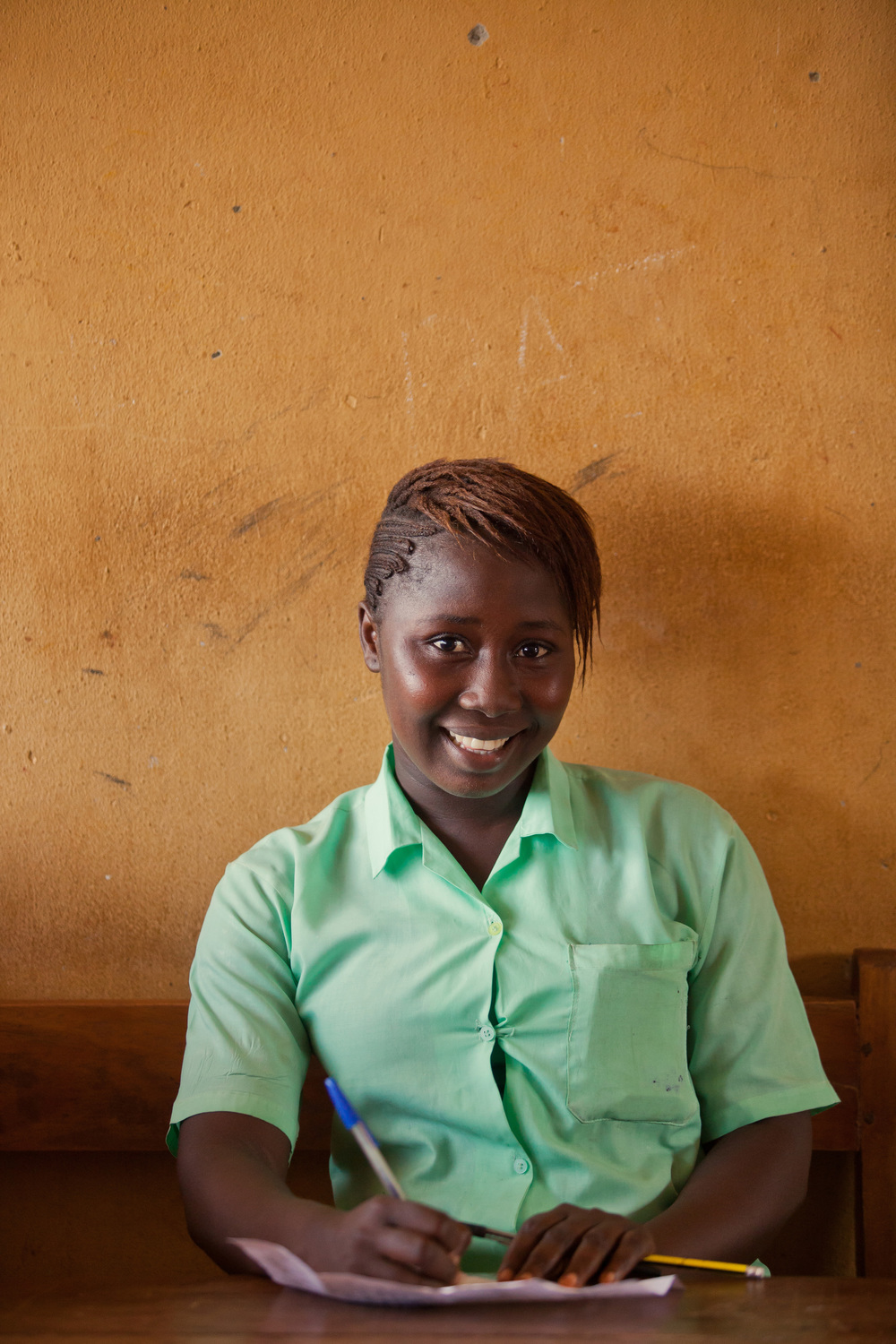 Isha's f amily was displaced by the war in Sierra Leone soon after she was born, and they had to leave their support network behind them. When Ebola hit the country last year, it claimed both of her parents. Isha, 15, is quick to smile and gets good grades. She's eager to be back in class after a year of no school.