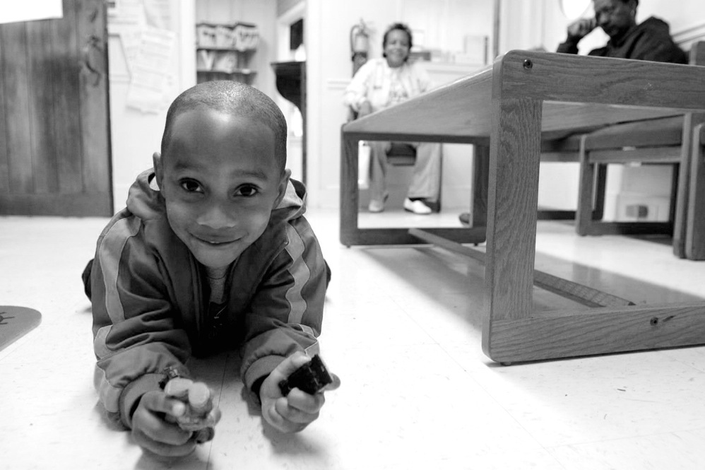 Marcus, 2, plays with toy cars in the waiting room as he waits for his mother to return from her exam.