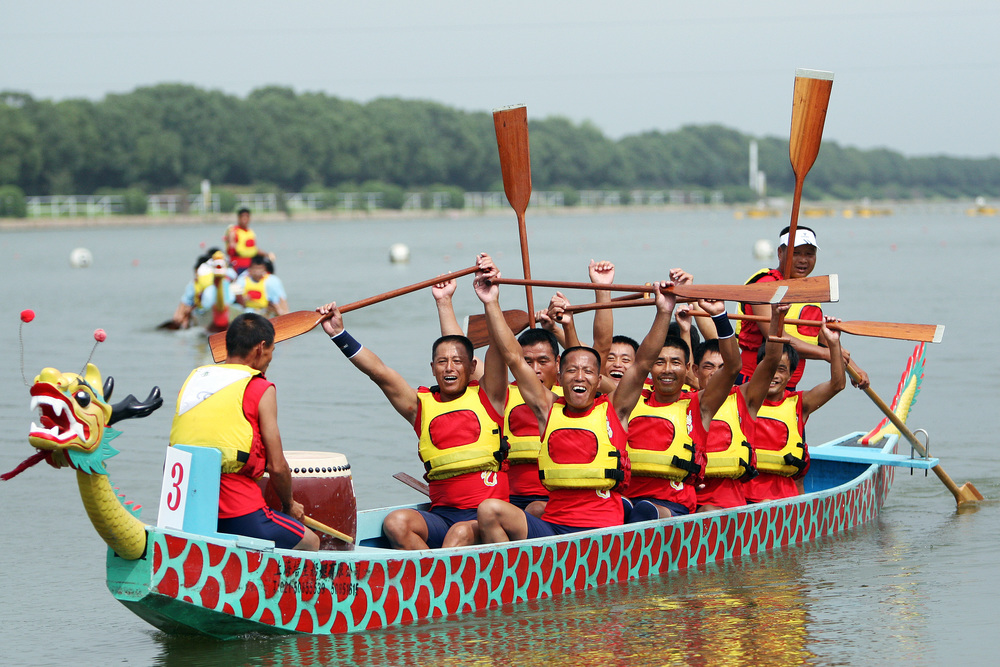 Members of China Team 2 celebrate their victory in the 250 meter dragon boat final race at Shanghai Aquatic Sports Center.