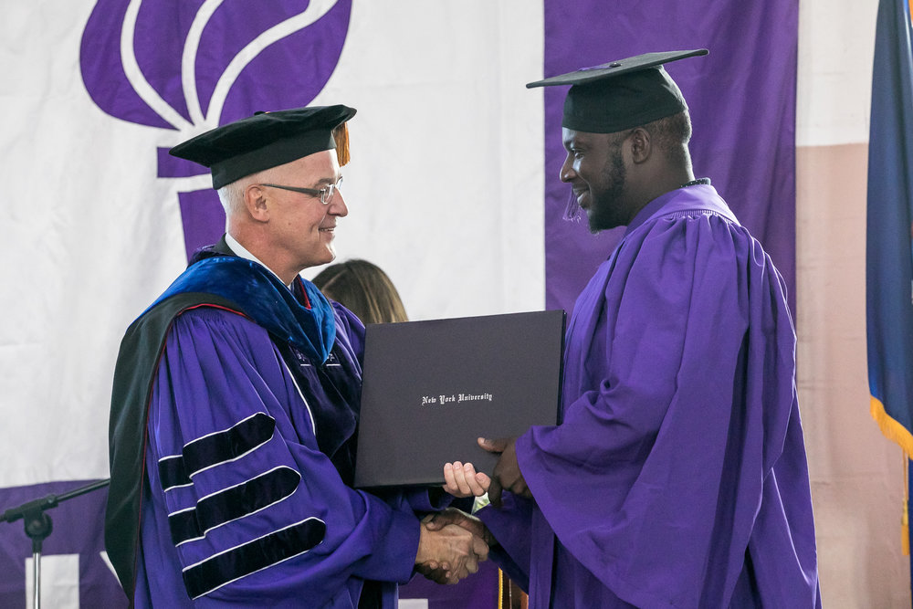 Ryan Burrell receives his diploma from President Hamilton. The graduates earned Associate of Arts Degrees from New York University in Liberal Studies.
