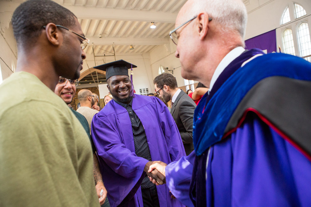Graduate Ryan Burrell shakes hands with New York University President Andrew Hamilton after the ceremony.