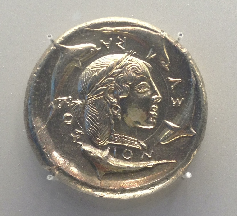 """The Demareteion Master"" : Dekadrachm with head of Arethusa. Sicily, about 470-465 BCE. Silver. One of the most celebrated in the MFA, Boston. This female head surrounded by dolphins is believed to be Arethusa, a nymph who transformed into a fountain on Ortygia, the home island of Syracuse. Demarete, the wife of Gelon I ( leader of Syracuse) was involved in the creation of this coin's design!"