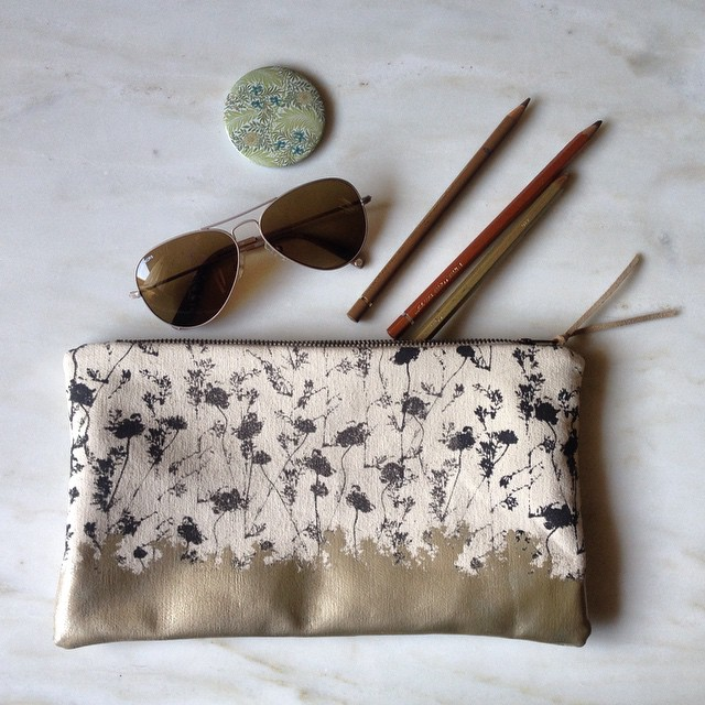 The #laurel purse bag with #almondgold #foil #screenprinted with special heat sensitive ink making the floral pattern 🔮magically ✨ disappear when touched #planetariumdesign #screenprintedbag