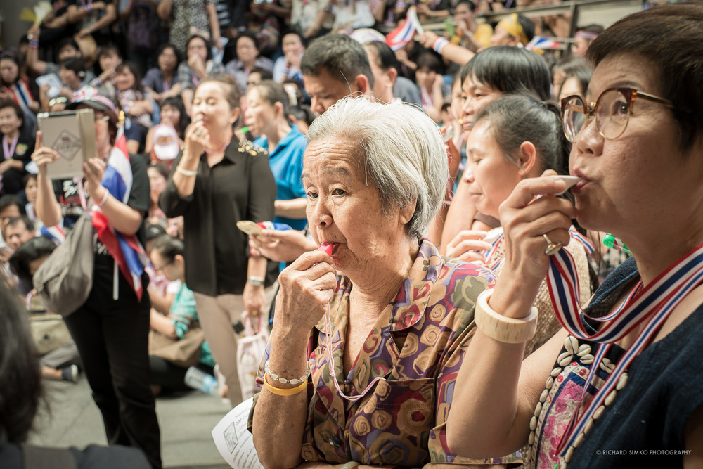 Blowing a whistle. It is an audible symbol of protests against Yingluck government.